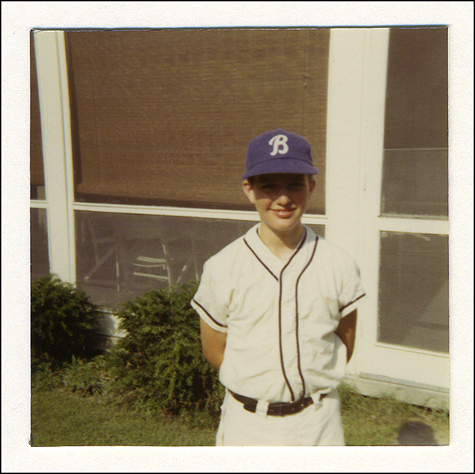 "Awwww. What a cute snapshot of me in my little league baseball uniform! So touching! Just LOOK at that smile! Well, folks, I'm here to tell ya that I HATED playing baseball! Every fiber in my body LOATHED every moment I had to endure – and for FOUR YEARS. Why was I doin' it? The old man. Yup, my dad apologized years later (he knew I hated it) by explaining that he was living vicariously through my participation in that gawdawful experience (and that's another reason why the subtitle to this series of blogs includes the word ""dysfunction""). Thanks a lot dad! If anything, though, this pix makes me crack up with laughter as I remember fondly HOW MUCH I HATED IT ALL! I've got nothing against ""Our National Pastime"" per se, I just don't wanna be doing it myself. The ""B"" on my cap? While everybody said it stood for ""Brighton"" (the town I grew up in), to me looking back it stood for ""Bullsh%#"" - as in what kind of a player I was and what I thought about the whole conspiracy to get me out of the house. Now, I'm not anti-sports (I competed at the state and national level in swimming in college / was the captain of the team, blah, blah, blah), I just didn't want to play baseball. Still, I'm REALLY GLAD I have this snapshot, and will archivally preserve it FOREVER as a reminder of what a complete dweeb I was (am?). 'Nuff said."